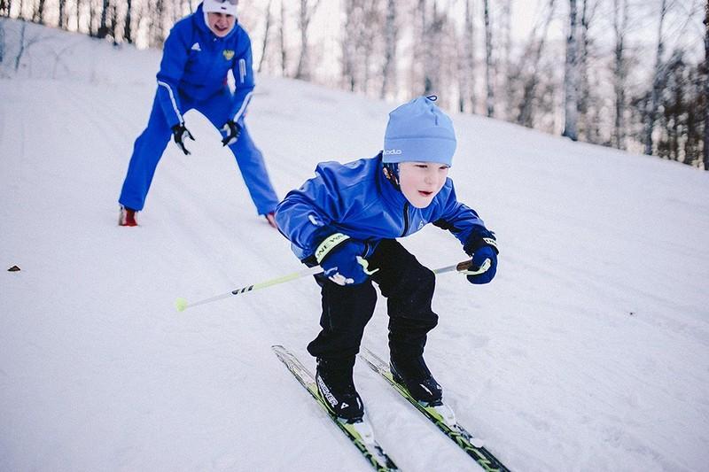 ребенок с тренером на занятии зимним видом спорта